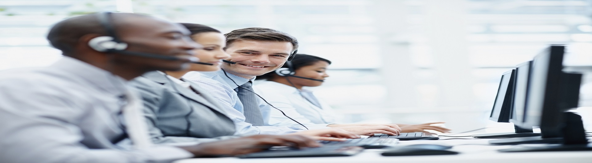 Portrait of business people working in front of computer with headphones